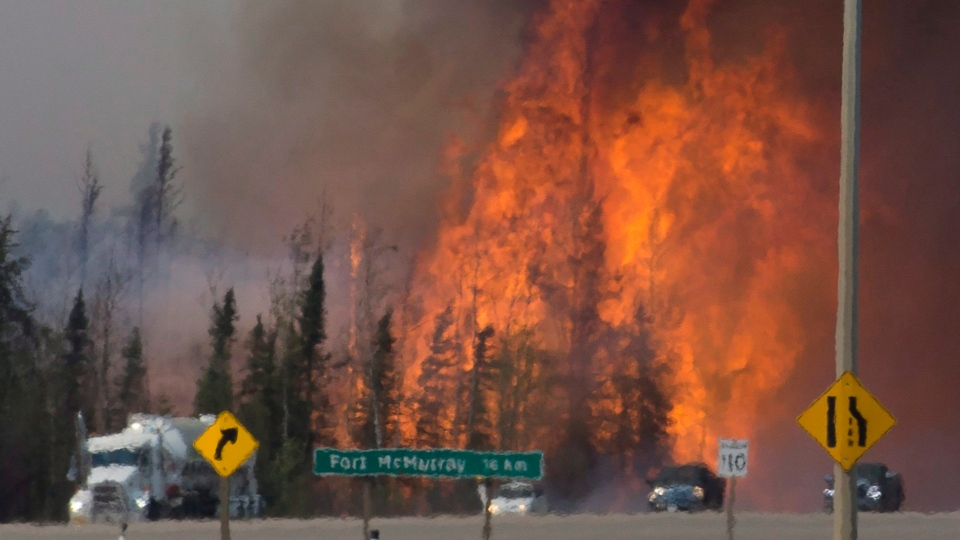 Heat waves are seen as cars and trucks try and get past a wild fire 16km south of Fort McMurray on highway 63 Friday, May 6, 2016. (Jonathan Hayward / THE CANADIAN PRESS)