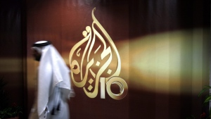 In this Wednesday Nov. 1, 2006 file photo, a Qatari employee of Al Jazeera Arabic language TV news channel walks past the logo of Al Jazeera in Doha. (AP / Kamran Jebreili, File)