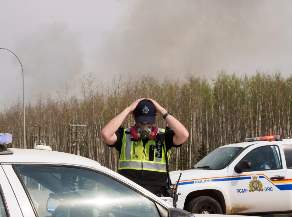 An RCMP officer puts on his gas mask before heading on the highway to Fort McMurray as wildfires are still burning out of control Saturday, May 7, 2016. (Ryan Remiorz / THE CANADIAN PRESS)