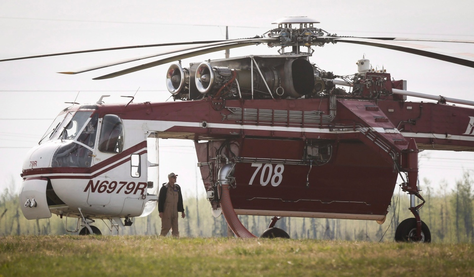 Crew members of a heavy lift helicopter helping with the Fort McMurray wildfires stand by their helicopter at a staging base near Conklin, Alta., Saturday, May 7, 2016. (Jeff McIntosh / THE CANADIAN PRESS)