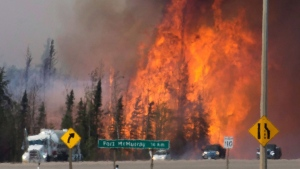 Heat waves are seen as cars and trucks try and get past a wild fire 16km south of Fort McMurray on highway 63 Friday, May 6, 2016 (Jonathan Hayward / THE CANADIAN PRESS)