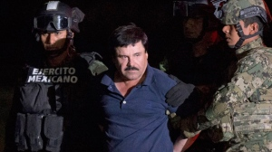 """In this Jan. 8, 2016 file photo, Mexican drug lord Joaquin """"El Chapo"""" Guzman is escorted by army soldiers  to a waiting helicopter, at a federal hangar in Mexico City, after he was recaptured from breaking out of a maximum security prison in Mexico. (AP / Rebecca Blackwell, File)"""