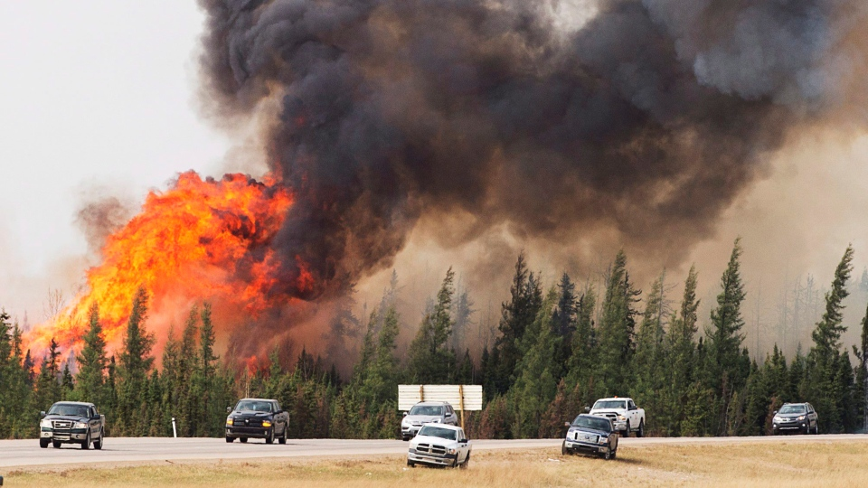 A convoy of evacuees from Fort McMurray, Alberta drive past wildfires that are still burning out of control as they leave the city Saturday, May 7, 2016.THE CANADIAN PRESS/Ryan Remiorz