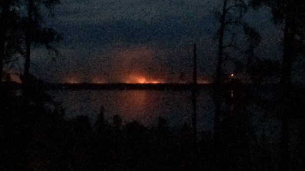 The glow of the forest fire can be seen over West Hawk Lake Saturday night, looking north from the town site.