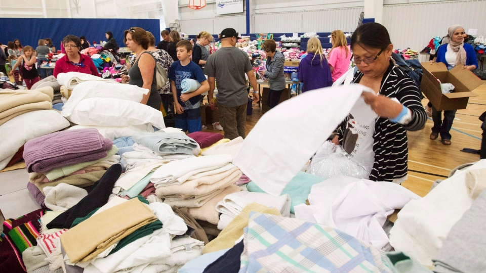 Evacuees from the Fort McMurray wildfires look through donated supplies at a shelter in Lac la Biche, Alta., on Friday, May 6, 2016. (Ryan Remiorz / THE CANADIAN PRESS)