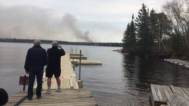 People watch as smoke from wildfires burning near Whiteshell Provincial Park rises in the distance on May 8, 2016.