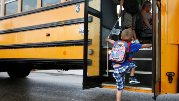 A student at Indian Lake Elementary in Kalamazoo, Mich., boards a bus on the first day of school on Sept. 4, 2012. (AP Photo/The Kalamazoo Gazette, Mark Bugnaski, File)