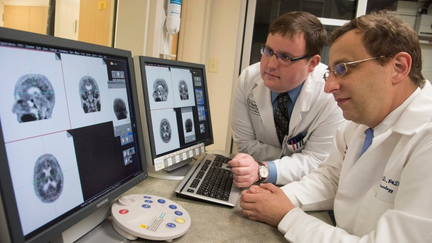 This photo provided by Washington University shows associate professor of neurology at Washington University School of Medicine Beau Ances MD, PhD, right, and Matthew Brier an MD/PhD student at the university, examining PET (positron emission tomography) scans of Alzheimer's disease patients, in St. Louis. (Robert Boston/Washington University via AP)