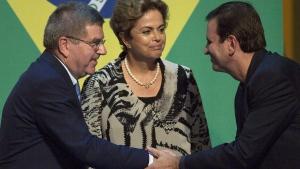 IOC President Thomas Bach, left, greets Rio de Janeiro Mayor Eduardo Paes as Dilma Rousseff smiles in Rio de Janeiro, Brazil, on Aug. 5, 2015. (Leo Correa / AP)