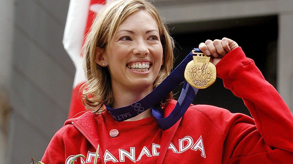 Canadian cross-country skier Beckie Scott displays her gold medal she was awarded at a ceremony in Vancouver, Friday, June 25, 2004. (THE CANADIAN PRESS/Chris Bolin)