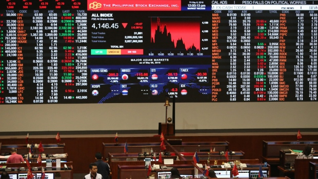 Filipino traders stand in front of the electronic board at the Philippine Stock Exchange at the financial district of Makati, south of Manila, Philippines, Friday, May 6, 2016. (AP Photo / Aaron Favila)