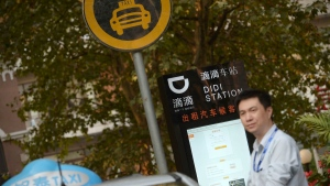 A taxi driver waits at a newly-installed Didi Station, a road-side stop for taxis booked by the Chinese car-hailing app Didi Kuaidi, which has since changed its name to Didi Chuxing, in Shanghai on Thursday, Oct. 15, 2015. (Chinatopix)