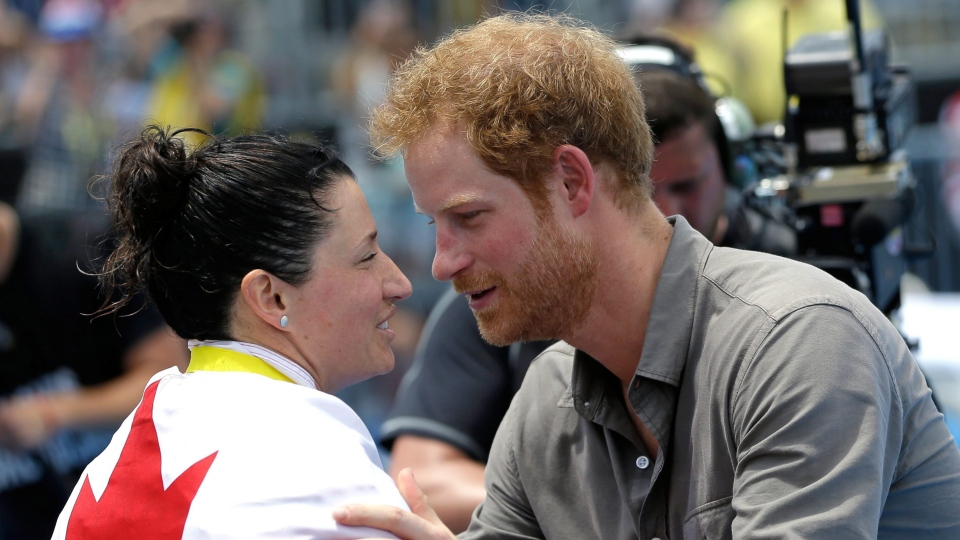 Britain's Prince Harry, right, awards Mireille Poulin, of Canada, the gold medal for the Women's 100 meter LC freestyle during the swimming events at the Invictus Games, Wednesday, May 11, 2016, in Kissimmee, Fla. (AP / John Raoux)