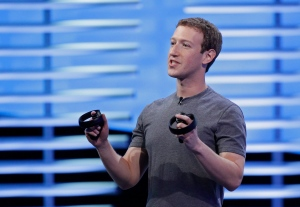Facebook CEO Mark Zuckerberg holds a pair of virtual reality handsets during the keynote address at the F8 Facebook Developer Conference Tuesday, April 12, 2016, in San Francisco. (AP Photo/Eric Risberg)