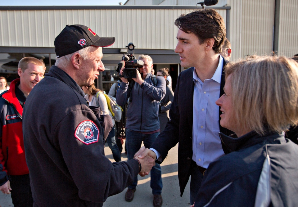 Prime Minister Justin Trudeau shakes hands with Fort McMurray fire chief Darby Allen as Alberta Premier Rachel Notley (right) looks on in Edmonton, Friday, May 13, 2016, before a flight to Fort McMurray. (THE CANADIAN PRESS/Jason Franson)