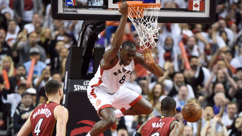 Toronto Raptors' Bismack Biyombo (8) dunks the ball over Miami Heat's Dwyane Wade (3) and Josh McRoberts (4) during the Eastern Conference semifinal in Toronto, on Sunday, May 15, 2016. (THE CANADIAN PRESS/Frank Gunn)