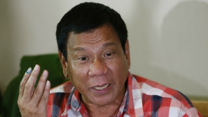 Then front-running presidential candidate Mayor Rodrigo Duterte gestures during his second news conference after voting in a polling precinct at Daniel R. Aguinaldo National High School, Matina district, his hometown in Davao city in southern Philippines on Monday, May 9, 2016. (AP / Bullit Marquez)
