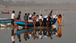Indian boatmen try to free a boat which got stuck due to low water level in Allahabad, India, Friday, April 8, 2016. (AP Photo/Rajesh Kumar Singh)