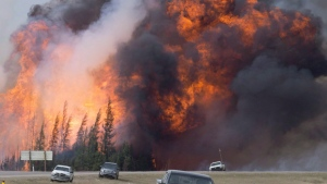 FILE - A wildfire rips through the forest by Highway 63, south of Fort McMurray, Alta., on Saturday, May 7, 2016. (THE CANADIAN PRESS/Jonathan Hayward)