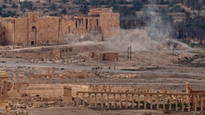 Russian soldiers stand on a road as smoke rises from a controlled land mine detonation in Palmyra, Syria, on April 14, 2016. (Hassan Ammar / AP)