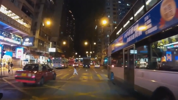 In this YouTube screengrab, a little girl is seen dashing across the street amid oncoming traffic in Hong Kong. (
