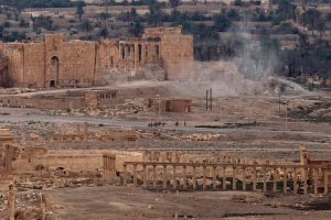 In this Thursday, April 14, 2016 file photo, Russian soldiers stand on a road as smoke rises from a controlled land mine detonation by Russian experts inside the ancient town of Palmyra, Syria. (AP Photo/Hassan Ammar, File)