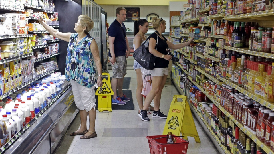 In this Friday, June 12, 2015, photo, grocery shoppers browse an aisle at a local grocery store in the Little Havana area of Miami. (AP Photo/Alan Diaz)
