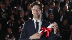 Director Xavier Dolan poses for photographers after being awarded the Grand Prix award for the film It's only the end of the world, during the awards ceremony at the 69th international film festival, Cannes, southern France, Sunday, May 22, 2016. (AP Photo/Joel Ryan)