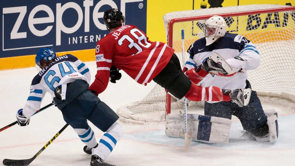 Canada's Boone Jenner, center, Finland's Mikael Granlund, left, and goalie Mikko Koskinen struggle for a puck during the Ice Hockey World Championships final match between Finland and Canada, in Moscow, Russia, on Sunday, May 22, 2016. (AP Photo / Ivan Sekretarev)