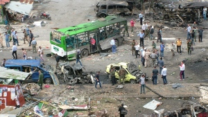 In this photo released by the Syrian official news agency SANA, Syrians inspect damages after a bombing attack at a bus station, in the coastal town of Tartus, Syria, Monday, May 23, 2016.  (SANA via AP)