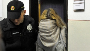 Slovakian model Maria Kukucova, right, hides her face in a scarf as she leaves a court after being taken into custody in Trencin, Slovakia, Thursday, April 10, 2014. (AP / CTK, Jak Koller)