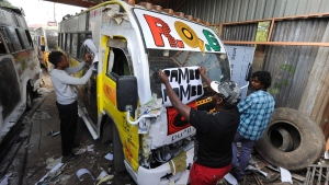 Artists put graffiti and stickers on a privately-owned public transport bus, popularly known as 'matatu' at a workshop in a suburb of Nairobi on April 14, 2016. (TONY KARUMBA / AFP)
