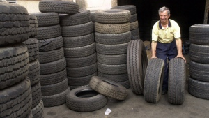 Tire store owner Manuel Vieira moves old tires in his shop in Caracas, Venezuela on Aug. 28, 2000. (AP Photo/Andres Leighton, File)