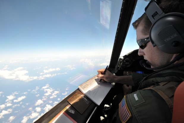 U.S. Navy LT JG Curtis Calabrese takes notes on board of a U.S. Navy Lockheed P-3C Orion patrol aircraft from Sigonella, Sicily, Sunday, May 22, 2016, searching the area in the Mediterranean Sea where the Egyptair flight 804 en route from Paris to Cairo went missing on May 19.  (AP Photo/Salvatore Cavalli)