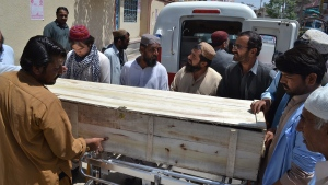 People stand near a coffin carrying a body one of the victims in a reportedly U.S. drone strike in the Ahmad Wal area in Baluchistan province of Pakistan, at a local hospital in Quetta, Pakistan, Sunday, May 22, 2016. (AP / Arshad Butt)