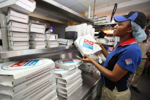 In this Sunday, Feb. 10, 2013, file photo, a worker prepares boxes at a Domino's pizza restaurant in Lagos, Nigeria. ( AP / Sunday Alamba)