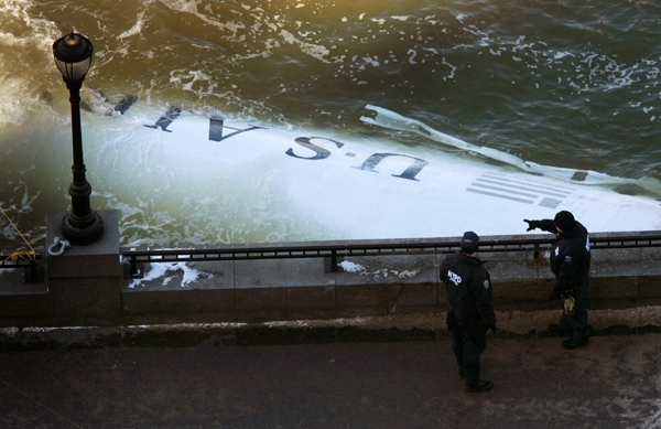 New York City police officers look over part of the US Airways Airbus 320 that crashed into the Hudson River as it sticks out of the water after it had been towed there for further inspection, Friday, Jan. 16, 2009. (AP / Seth Wenig)