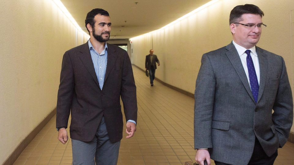 Omar Khadr, left, leaves court with his lawyer Nate Whitling, right, after a judge ruled to relax bail conditions in Edmonton on Sept. 18, 2015. (Amber Bracken / THE CANADIAN PRESS)