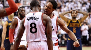 Toronto Raptors centre-forward Bismack Biyombo and DeMar DeRozan celebrate during the last seconds of second half Eastern Conference final NBA playoff basketball action against the Cleveland Cavaliers in Toronto on Monday, May 23, 2016. THE CANADIAN PRESS/Frank Gunn