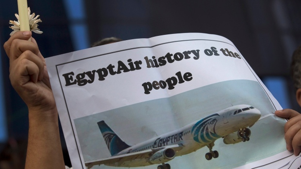 An Egyptian journalist holds a candle and a poster supporting EgyptAir during a candlelight vigil for the victims of EgyptAir flight 804 in front of the Journalists' Syndicate in Cairo, Egypt, Tuesday, May 24, 2016. (AP / Amr Nabil)