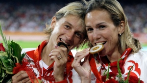 In this Sunday, Aug. 17, 2008 file photo bronze medal winner Ekaterina Volkova bite their medals after the women's 3000-meter steeplechase at the Beijing 2008 Olympics in Beijing. (AP /Petr David Josek, file)