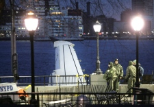 Emergency personnel stand near a part of the sticking out of the Hudson River in New York, Friday, Jan. 16, 2009. Investigators brought in a giant crane and a barge Friday to help pull the jetliner from the river. (AP / Seth Wenig)