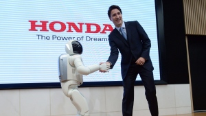 Prime Minister Justin Trudeau meets Honda Robot Asimo as he visits Honda Motor Co. headquaters in Tokyo, Japan on Tuesday, May 24, 2016. (Sean Kilpatrick / THE CANADIAN PRESS)