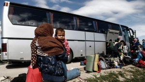 Migrants board a bus during a police operation at a makeshift refugee camp at the Greek-Macedonian border near the northern Greek village of Idomeni, Wednesday, May 25, 2016. (Yannis Kolesidis/ANA-MPA via AP)