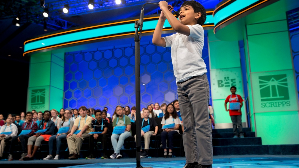 Six-year-old Akash Vukoti, of San Angelo, Texas, the youngest contestant in the 2016 National Spelling Bee, pulls down his microphone to compete in the preliminaries of the Bee at National Harbor, Md., on Wednesday, May 25, 2016. He spelled his word correctly. (AP Photo/Jacquelyn Martin)