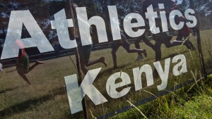 FILE - Athletes run past a sign for Athletics Kenya at the Discovery cross country races, in Eldoret, Kenya, on Sunday, Jan. 31, 2016. (AP Photo/Ben Curtis)