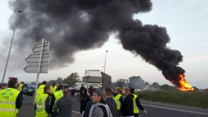 Union activists guard a traffic circle near the Normandie Bridge outside of Le Havre where a pile of burning tires gas thrown up a big cloud of smoke during a blockade action on Thursday, May 26, 2016. (AP / Raphael Satter)