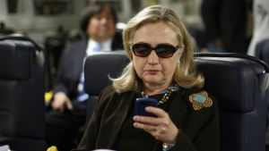 Then-Secretary of State Hillary Rodham Clinton checks her Blackberry from a desk inside a C-17 military plane upon her departure from Malta, in the Mediterranean Sea, bound for Tripoli, Libya on Oct. 18, 2011. (AP / Kevin Lamarque)