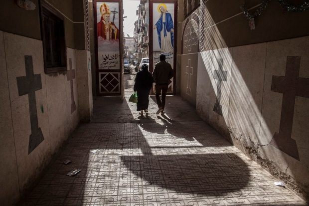 In this Tuesday, Jan. 6, 2015 file photo, Coptic Christians walk outside St. Markos Church in Minya, south of Cairo, Egypt. (AP / Roger Anis)