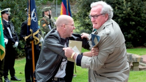 Canadian Ambassador to Ireland Kevin Vickers, right, wrestles with a protester during a ceremony to remember the British soldiers who died during the Easter Rising at Grangegorman Military Cemetery, Dublin Thursday May 26, 2016. (SWNS)